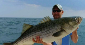 A customer at The Dock Outfitters with a 53-pound striped bass he caught. (Photo: Dock Outfitters)
