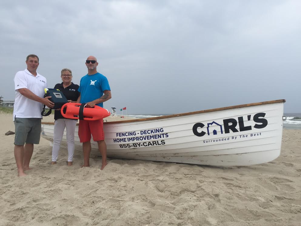 Carl DelPizzo Jr. and Cindy Kuhmann (of Carl's Fencing, Decking, & Home Improvements) presented Island Beach Motor Lodge, Ocean Lifeguard R.J. Hager with an Automated External Defibrillator