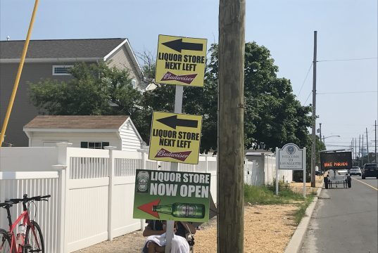 A liquor store employee holds a sign on Route 35 advertising the business. (Photo: Daniel Nee)