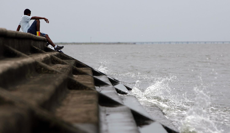 A man sits beside a levee on Lake Pontchartrain, New Orleans, La. (Credit: James Joel/ Flickr)