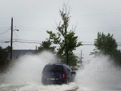 A vehicle speeds down a flooded street in a barrier island community. (Photo: Daniel Nee)