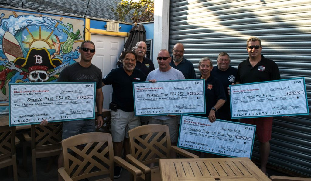 Checks presented to local organizations from the Bum Rogers annual block party, 2019. (Photo: Daniel Nee)